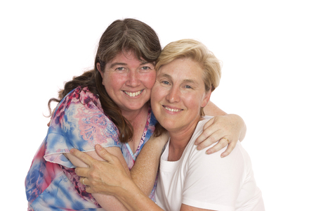 Two close friends hugging for a photo, real middle aged women.
