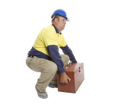 Ein Mann, der eine gute Hebetechnik verwendet, um seinen Werkzeugkasten zu bewegen. Sicherheitskonzept. Standard-Bild