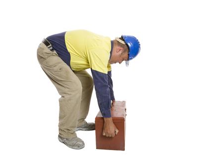 Un uomo che usa una tecnica di sollevamento scadente per spostare la sua cassetta degli attrezzi. Concetto di sicurezza.