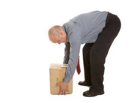 Mężczyzna wykorzystujący słabą technikę podnoszenia do przesuwania pudła. Koncepcja bezpieczeństwa.