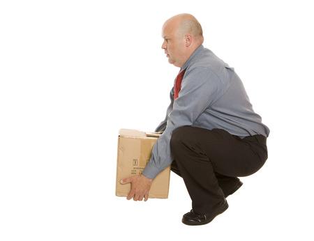 Un uomo che usa una buona tecnica di sollevamento per spostare una scatola. Concetto di sicurezza. Archivio Fotografico