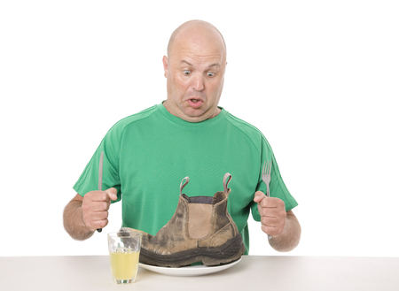 A man eating a meal that is tasteless and tough as boots, concept and sayings. Stock Photo