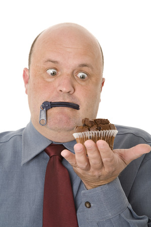A man with lips zipped tempted by a cup cake, healthy eating concept. Stock Photo