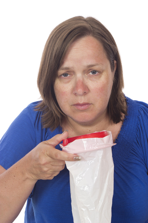 A mature woman with a sick bag feeling nauseous Stockfoto