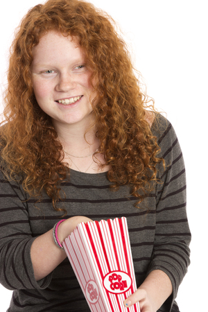 A teen with beautiful long curly hair, eating popcorn.