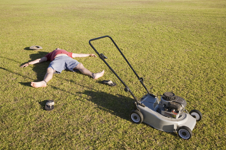 An exhausted man lying on the ground collapsed after mowing a huge lawn.