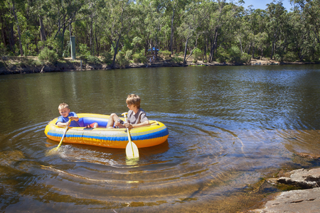 Two boys paddling in a rubber raft on an Australian river.