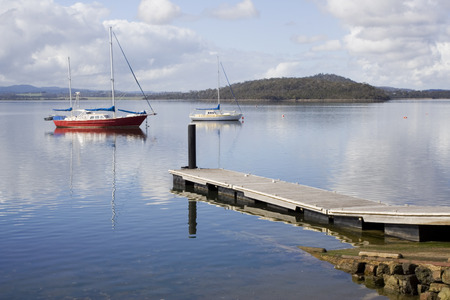 A small boat and pier with calm and reflective water in beautiful Tasmania.