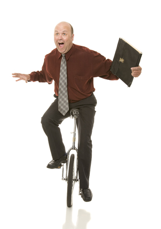 A businessman riding a unicycle.