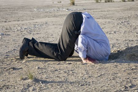 A powerful denial concept, man with his head in the sand. Stock Photo