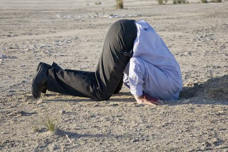 Een krachtig ontkenningsconcept, man met zijn hoofd in het zand. Stockfoto