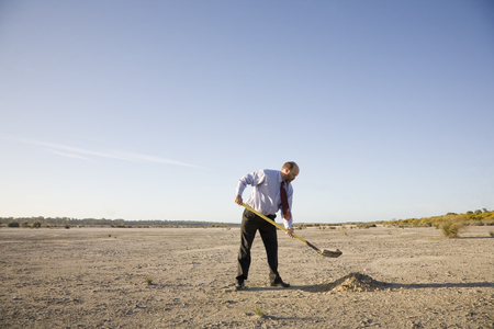A businessman digging a hole, perhaps to bury his head in the sand. Concepts. Stock Photo