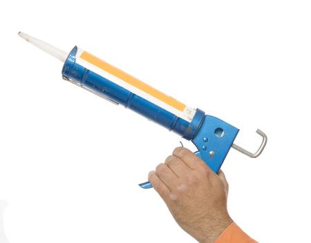 A hand using a caulking gun, on white. Reklamní fotografie