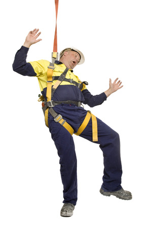 A worker falling over and wearing safety harness.