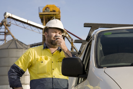 A maintenance worker talking on a radio at his vehicle, with site in background.