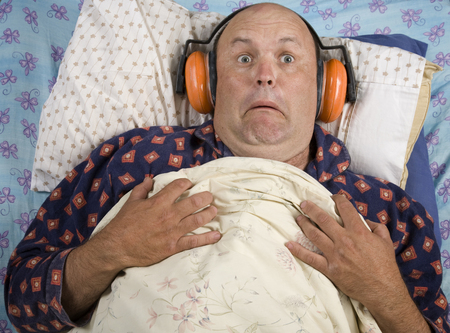 A man trying to sleep with noise, wearing industrial ear muffs.