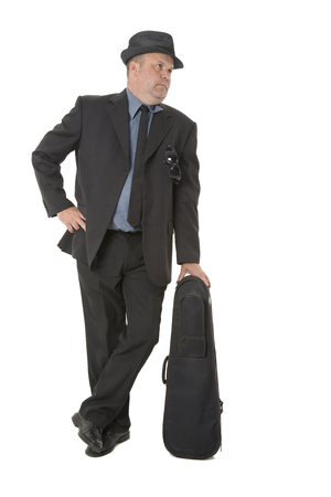 A man in suit leaning on a violin case.