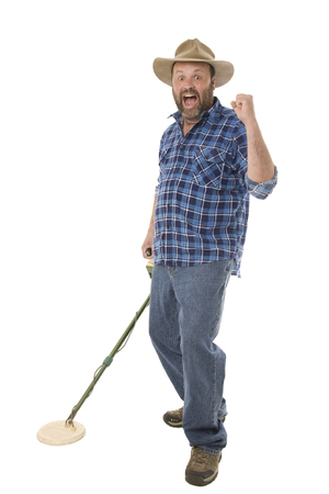 A man using a metal detector searching for treasure.