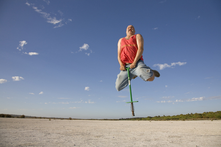 A man using a pogo stick at a desolate location. Stock fotó