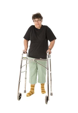 An elderly woman walking using a Zimmer Frame.