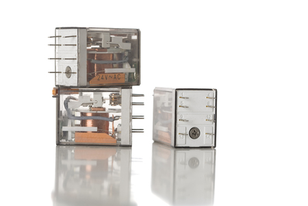 Three electrical control relays on white.