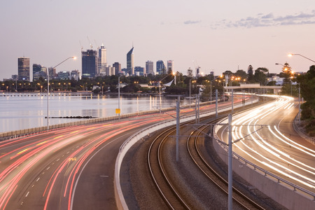 Perth city in the morning with the freeway and cars making a trail towards the city.