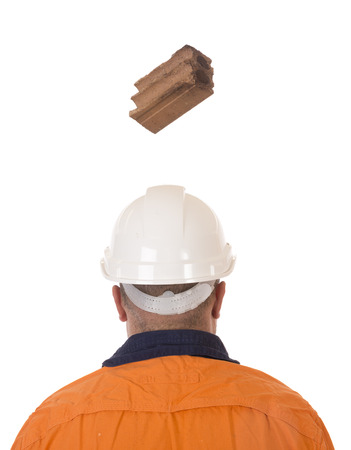 A brick falling from height towards a workers head which is protected by a safety helmet.