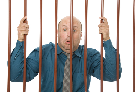 businessman in jail behind bars with a sad expression.