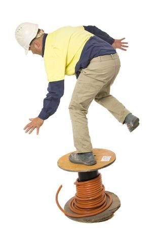 Un homme utilisant un tambour de câble au lieu d'une échelle, glisse et tombe.