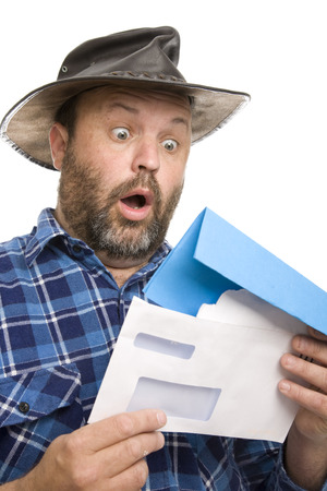 A man receives a bill in the mail and has a shocked expression. 版權商用圖片