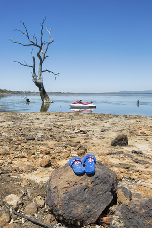 Australian thongs on a rock with an Aussie lake in the background.