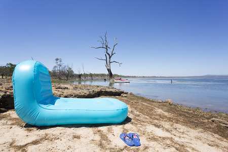 An inflatable pool toy at the side of a lake with Australian themed thongs in foreground.