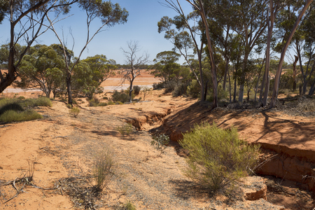 An eroded gully leading into a flat dry lake in the arid Australian outback.