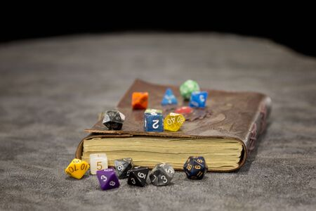 An old spell book with role playing dice piled around it.