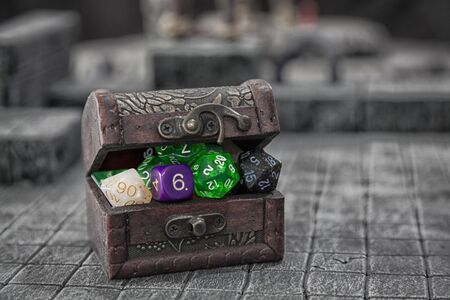A treasure chest bulging with dice for role palying game.
