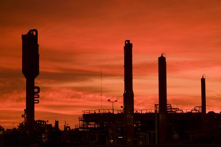 Industry silhouetted against an orange sky. Banco de Imagens