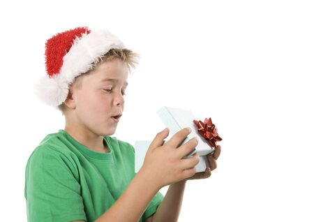 A boy opening a Christmas gift, looking inside box.