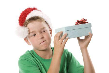 A curious boy examining his Christmas present.
