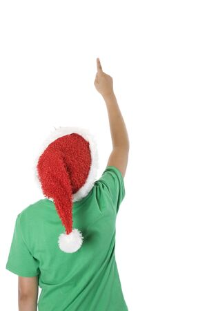 Rear view of a child wearing Santa hat, looking up and pointing, on white.