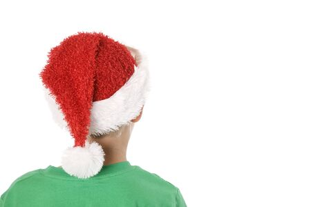 A rear view of a child wearing a Santa hat with copy space. Banco de Imagens
