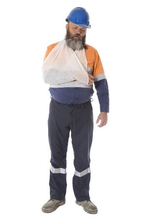 A full length image of an industrial worker injured in an accident with arm in sling, isolated on white.