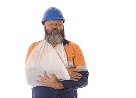An industrial worker with arm in sling with a pained expression.