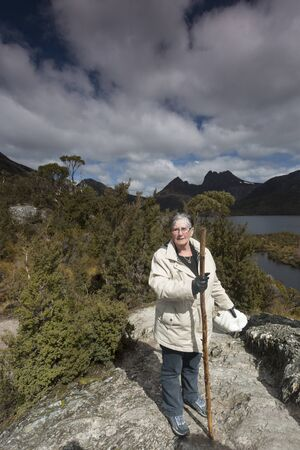A senior woman on a walking trail with Cradle Mountain in the background.