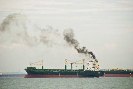 polluting: A cargo ship emitting black smoke polluting the air