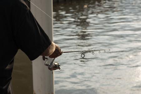 tropical fresh water fish: A man use fishing rod to fish from Chao Phraya River, Bangkok, Thailand Stock Photo