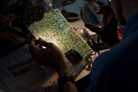 mainboard: Engineer looking at a Television Mainboard Stock Photo