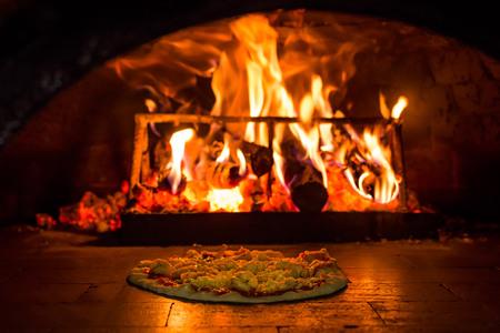 Kokende pizza in een bakstenen oven met houtvuur Stockfoto