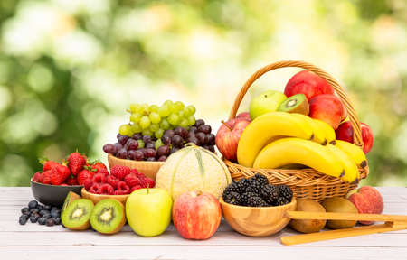 Group Healthy fresh fruit in a wooden basket, With vitamins c from bananas, kiwi, grapes, raspberries, blueberries, and blackberries, good for the body and diet food on the table in nature background. Stock Photo