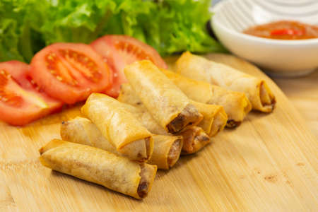 The image of fried spring rolls with vegetable filling as a snack or as a meal in every meal for a healthy Thai style meal in a beautiful wooden backdrop.