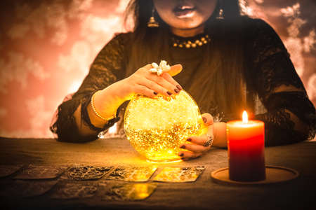 A picture of a woman holding a candle to perform magic rituals and mysteries about superstition in the concept of Divine magic & occultism on the old wooden table.
